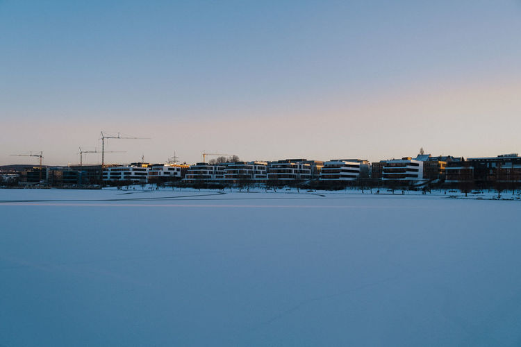Snow covered buildings against clear sky