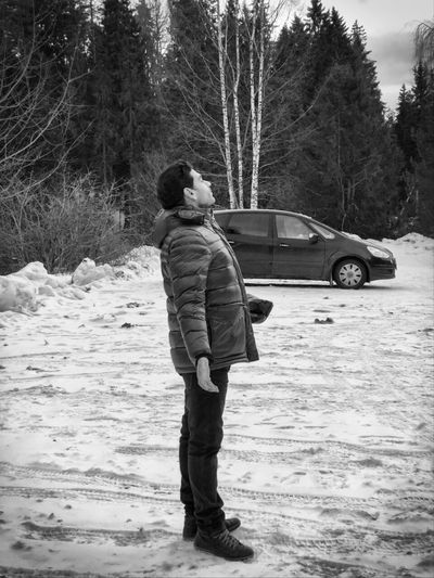 Rear view of man with umbrella standing on snow covered land