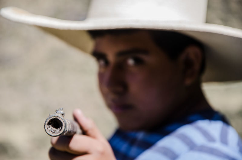 Close up face of boy with hat pointing with a rifle Rifle Aiming Army Military Shotgun Weapon Angry Childhood Hat Face Fighting Freedom Hunter Little Male People person Portrait Practice Serious Shooter Soldier Target War Play Gun Defense Power Security