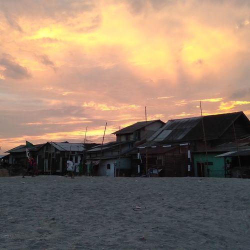 Houses on beach against sky during sunset