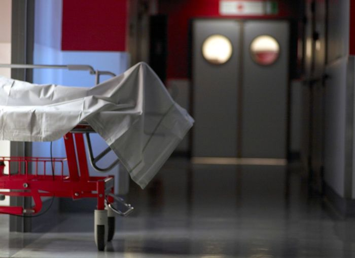 Dead person covered with sheet gurney in hospital corridor