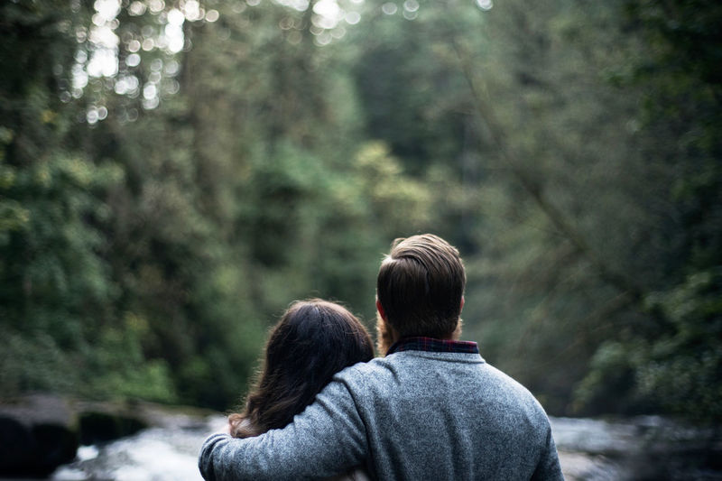 Rear view of couple by river in forest