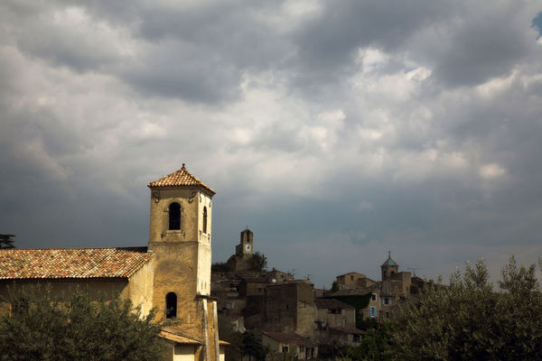 View of the village of Lourmarin, during a storm Provence Rain Storm Stormy Weather Sunlight Architecture Bell Tower Building Exterior Climate Change Cloud - Sky Cross Day Heat History Landscape No People Outdoors Sky Storm Clouds Sunlight And Shadow Temperature Tranquility Tree Village Village View