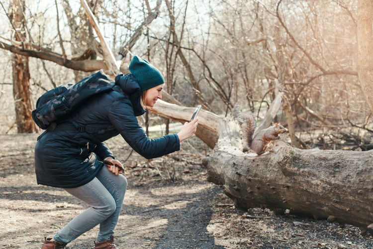 Side view of woman photographing squirrel in forest