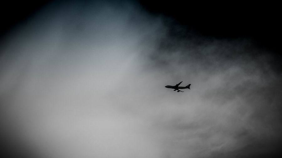 Low angle view of silhouette airplane against sky