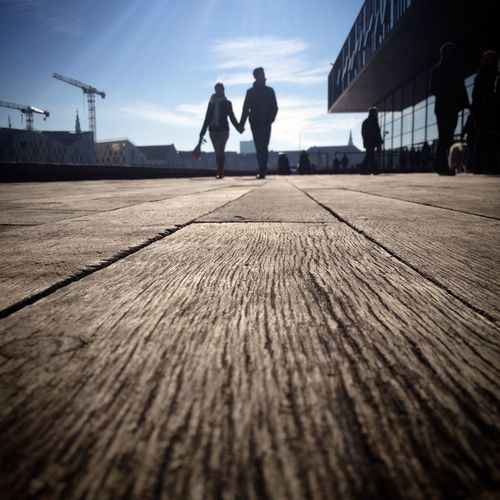 Surface level view of couple walking on wooden walkway