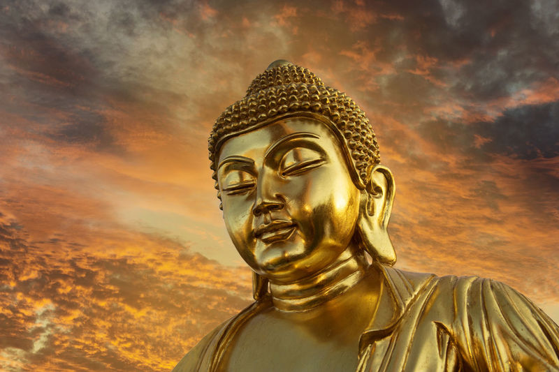 Golden Buddha Cloud - Sky Gold Gold Colored Human Representation Idol Low Angle View Male Likeness No People Outdoors Religion Sculpture Sky Spirituality Statue Sunset