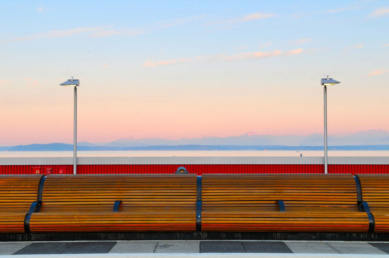 Empty Benches Against Sky During Sunset
