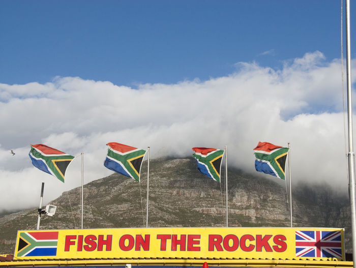 """Low angled shot of """"Fish On The Rocks"""" in Hout Bay, South Africa Blue Cloud Cloud - Sky Cloudy Colorful Culture Day Fish On The Rocks Hout Bay Information Information Sign Multi Colored No People Outdoors Pole Restaurant Sky South Africa South African Flags Variation Wind Yellow"""