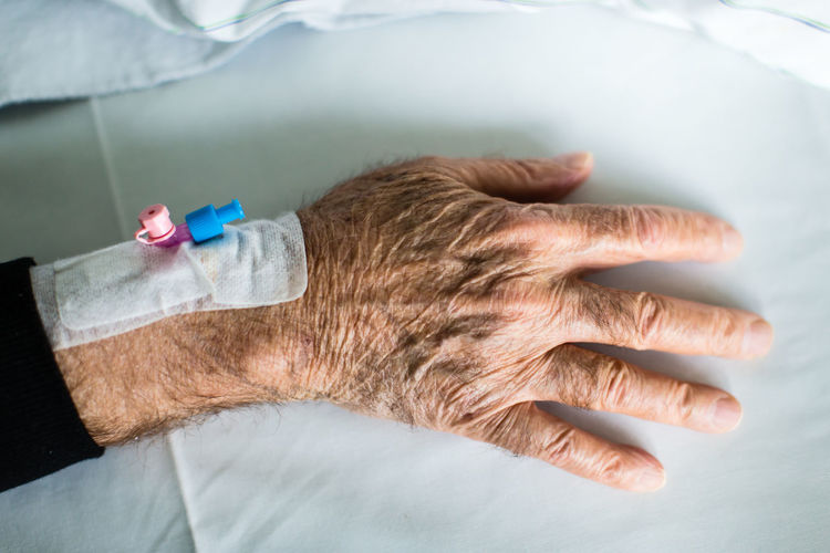 Cropped image of senior man hand in hospital