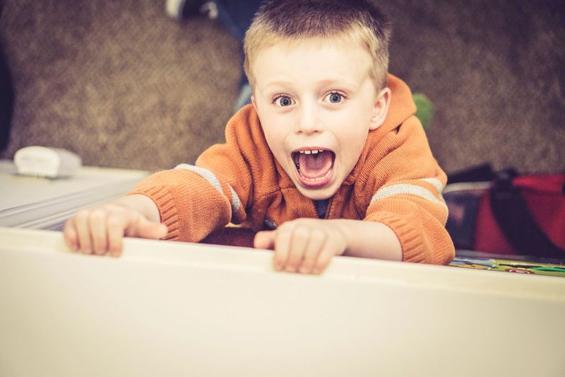 High angle portrait of playful boy screaming outdoors