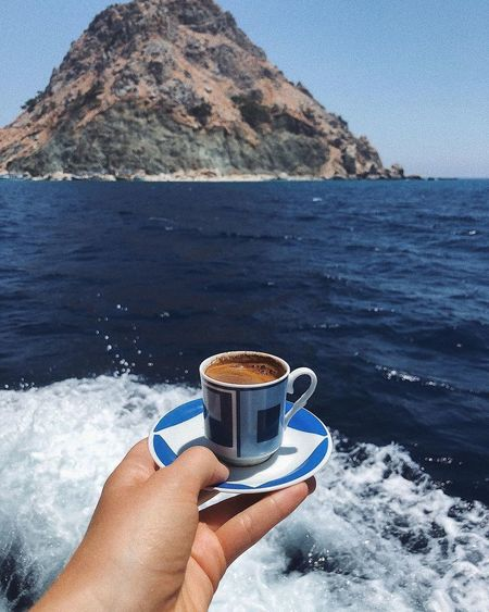 Hand holding coffee cup by sea