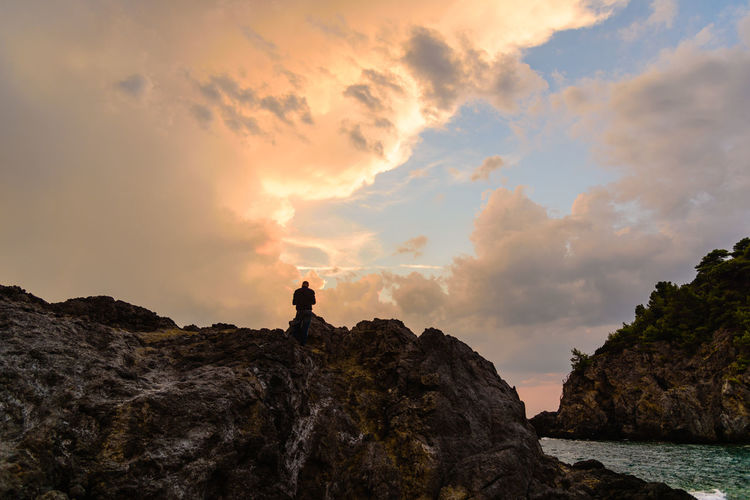Beauty In Nature Cliff Cloud - Sky Geology Men Mountain Nature Non-urban Scene Outdoors Physical Geography Remote Rock Formation Scenics Sky Solitude Standing Sunset Tourism Tourist Tranquil Scene Tranquility Travel Destinations Vacations End Of Summer