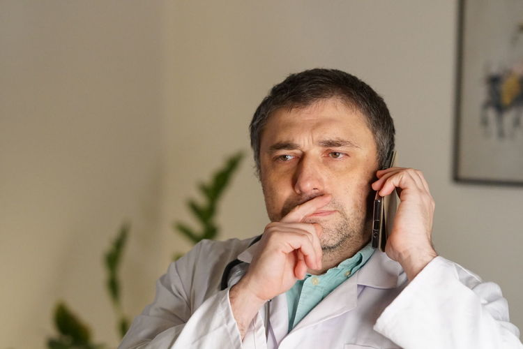 Mature Doctor Using Phone Against Wall
