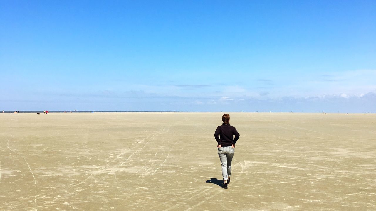 sky, lifestyles, one person, real people, leisure activity, land, full length, scenics - nature, rear view, beauty in nature, day, men, non-urban scene, casual clothing, standing, nature, horizon, copy space, tranquil scene, beach, outdoors, climate, salt flat