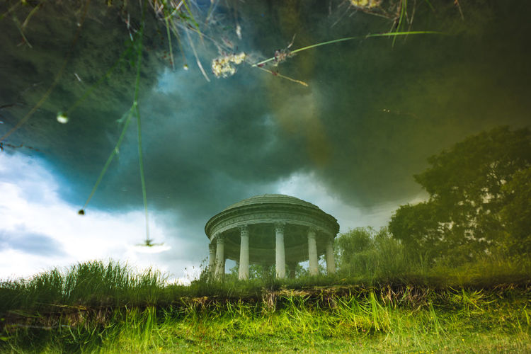 The Temple of Love in the gardens of Trianon. Queen Marie Antoinette's garden Pavilion at Versailles in France. Abstract view of abstract times. Abstract Photography Temple Of Love Architecture Beauty In Nature Building Exterior Built Structure Cloud - Sky Day Environment Field Grass Green Color Land Mystery Nature No People Outdoors Plant Scenics - Nature Sky Tree Upside Down