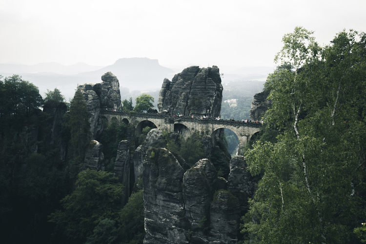 Bridge over rock formation against sky