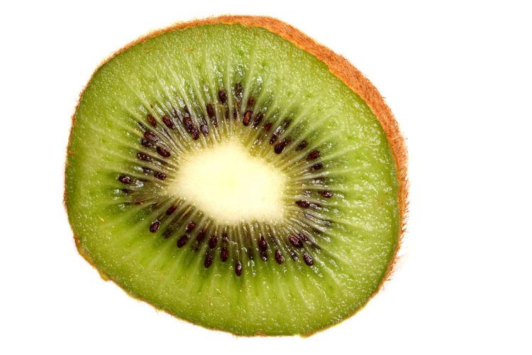 Close-up of kiwi slice over white background