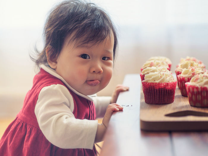 Portrait Of Cute Girl With Cupcakes