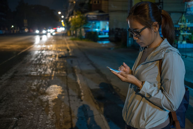 Young woman using mobile phone while standing in city at night