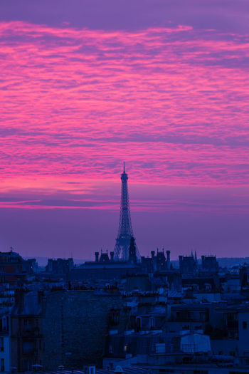 Eiffel tower in city against cloudy dramatic sky during sunset