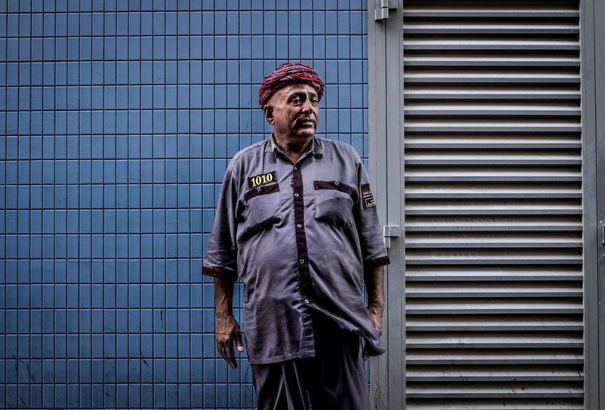 Outdoors Travel Dubai Urban Life One Person Streetphotography Portrait Photography Check This Out Standing Street Photography Photography Fujifilm Urban Street Work Person Pattern Life Style Portrait Composition Watchman Blue BYOPaper! The Portraitist - 2017 EyeEm Awards The Street Photographer - 2017 EyeEm Awards
