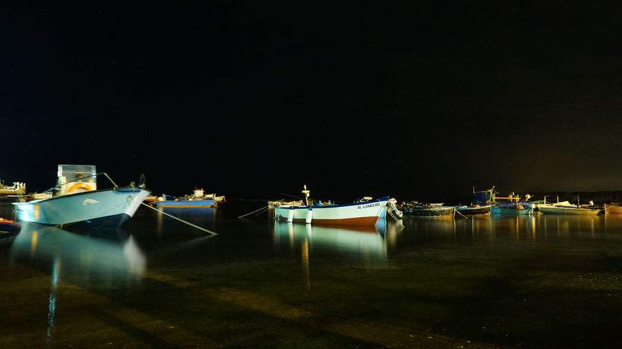 Boats moored in sea against clear sky at night