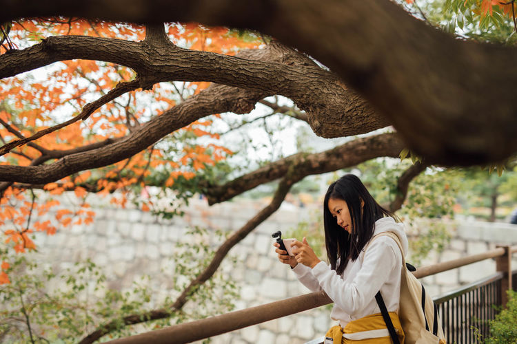 Portrait of young woman taking photo using mobile phone under a tree at the riverside