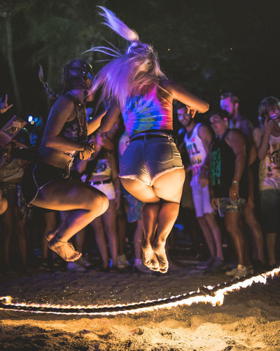 Jump up Night Group Of People Event Enjoyment Women Nightlife Adult Leisure Activity Real People Motion Illuminated Crowd Celebration People Flames Burning Rope Skipping Jumping Jump Holiday Thailand Shorts Denim Blonde