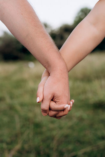 Close-up of couple holding hands outdoors against blurred background