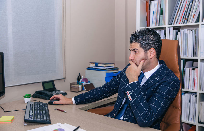 Serious businessman with jacket and tie looking computer in the office Business Busy Company Horizontal Man Suit Working Business Finance And Industry Businessman Caucasian Chairman Chief Concentration Device Executive  Headquarters Jacket Job Male One Person Portrait Serious Smart Phone Sucess Technology