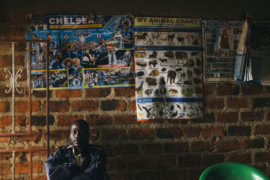 Africa African Brick Wall Football Football Fan Home Indoors  Looking At Camera Man One Man Only One Person Poor  Posters Real Life Real People Sitting Supporter Team Village