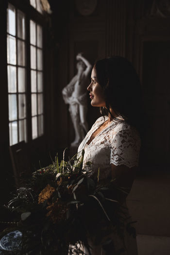 Side view of woman looking at window
