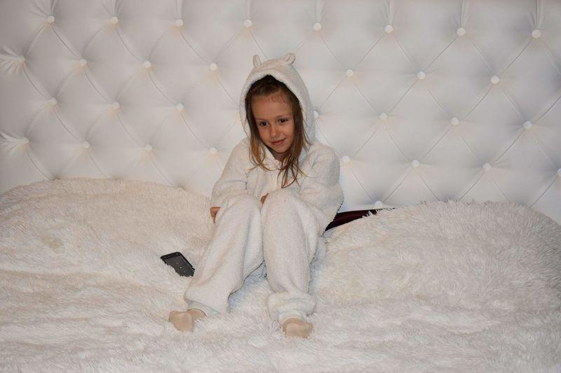 Full length of cute girl sitting on sofa