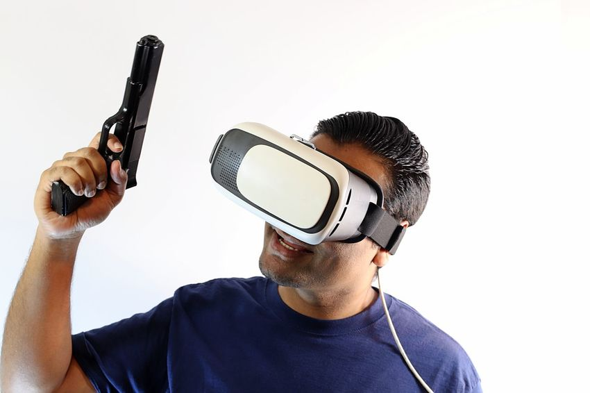 Young man with virtual reality headset holding gun wearing gloves holding one arm up with gun in hand Console Display Futuristic Gamer Gaming Glasses Gloves Goggles Gun Headset Innovation New Pistol Playing Riffle Role Playing Game Shooter Shooting Technology Virtual Virtual Reality War Weapon White Background Wireless Technology