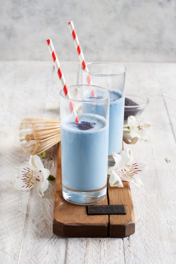 Butterfly pea blue matcha powder and a spoon top view Blue Matcha Foam Froth Latte Milk Whisk Butterfly Pea Powder Breakfast Drink Tea Antioxidant White Close Up Bowl Flowers Matcha Blue Dried Food Healthy Natural Organic Trend Vegan Vegetarian Clitoria Clitoria Powder Healthy Detox Thailand