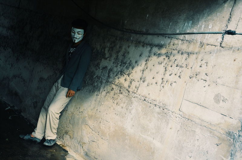 Man Wearing Mask While Standing Against Wall