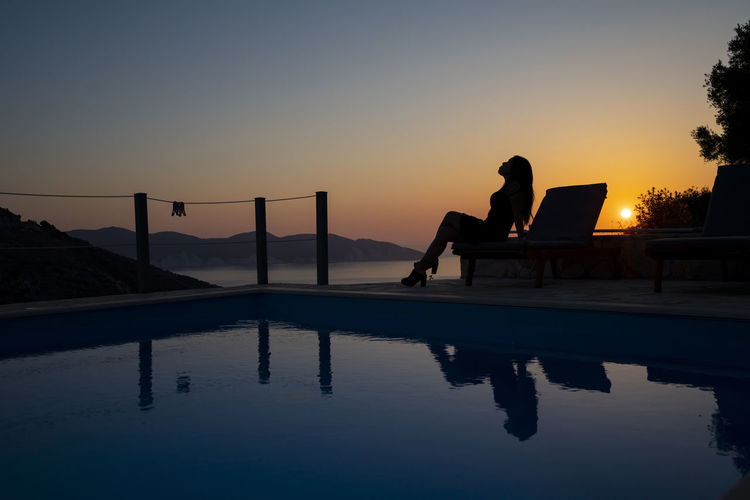 Silhouette man sitting by swimming pool against sky during sunset