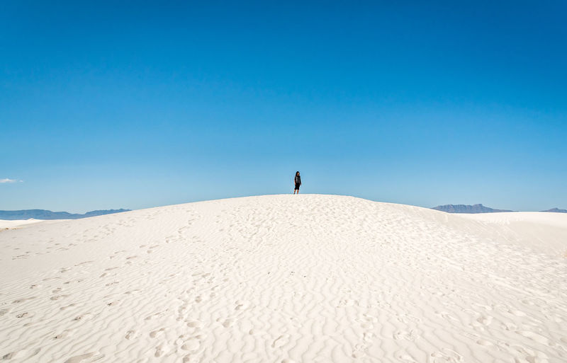 Woman Standing On Sand Against Blue Sky At Desert