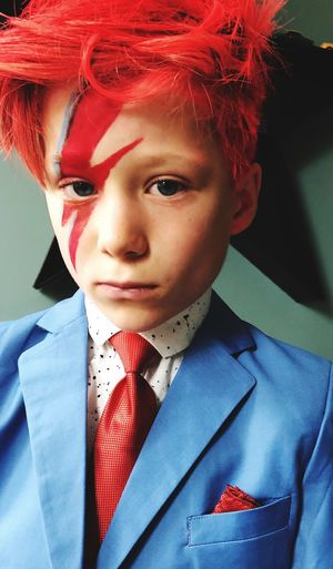Portrait Of Serious Well-Dressed Boy With Face Paint At Home