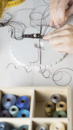High angle view of woman working with thread on table