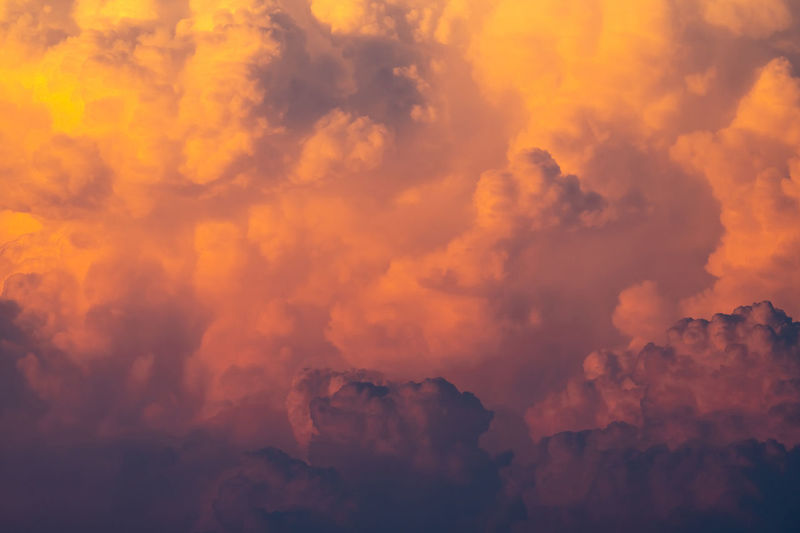 Yellow, orange fluffy clouds on sunset sky background. art picture of orange clouds texture.