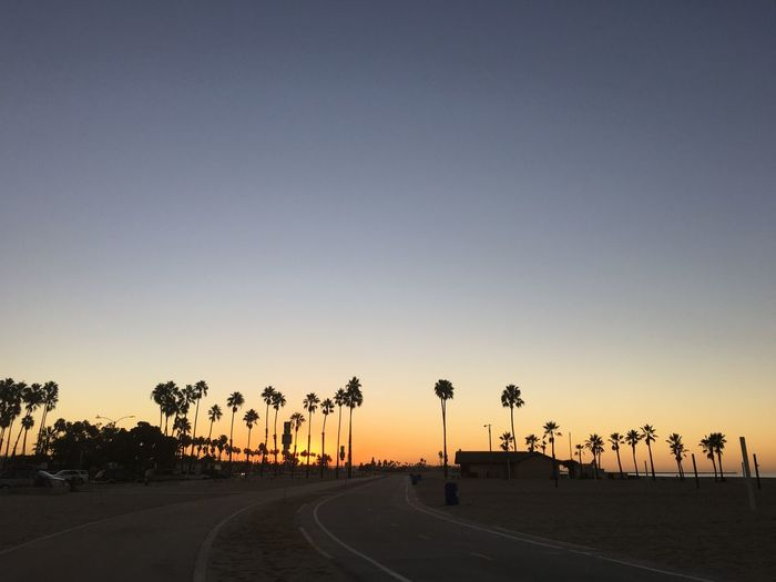 Road leading towards beach against sky during sunset