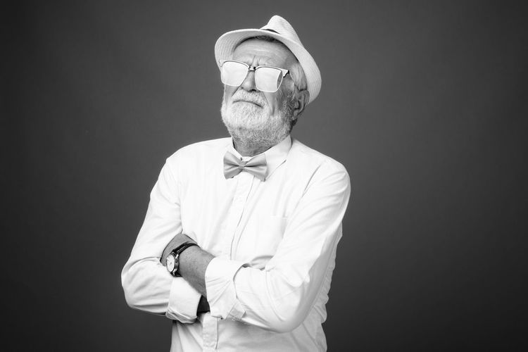 Man wearing hat while standing against black background