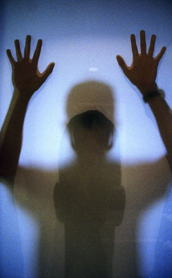 Low section of person with shadow in hands
