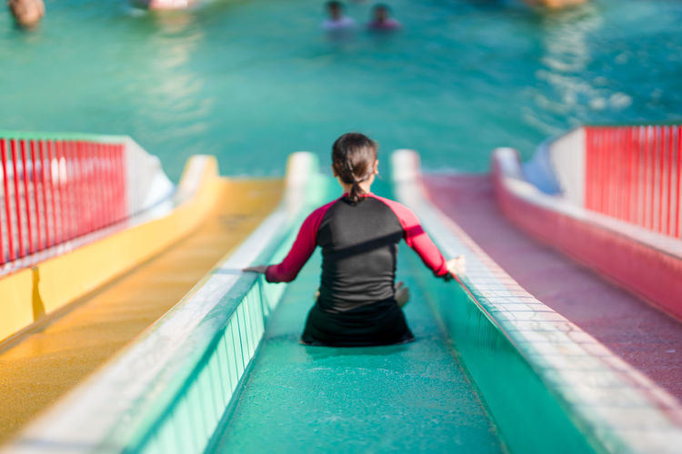 Rear view of woman sliding in water park