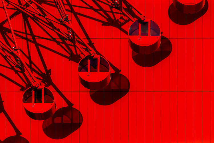 Low angle view of illuminated lanterns hanging on red wall