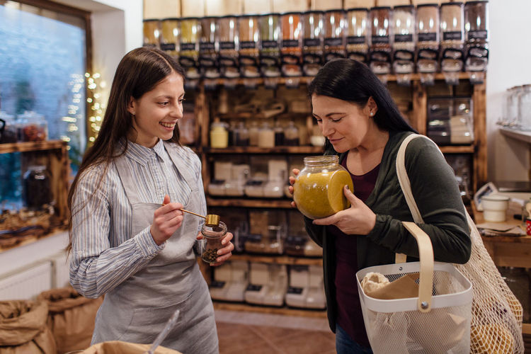 Woman smelling fresh spices in jar at package free grocery store. Customer buying spices in bio shop. Zero Waste Plastic Free Package Shop Store Raw Food Food Refill Organic Shopping Business Homemade Horizontal Grocery Bulk Interior Customer  Assistant Shopkeeper Two People Fresh Spice Bio Eco