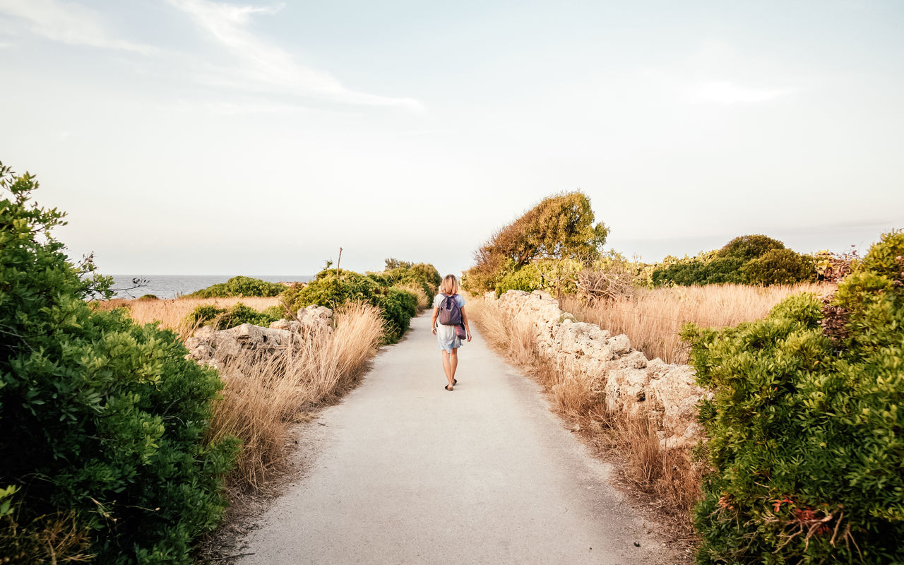 real people, full length, one person, rear view, casual clothing, leisure activity, day, nature, walking, sky, plant, road, lifestyles, sea, outdoors, water, beauty in nature, scenics, standing, grass, horizon over water, tree, young adult, people