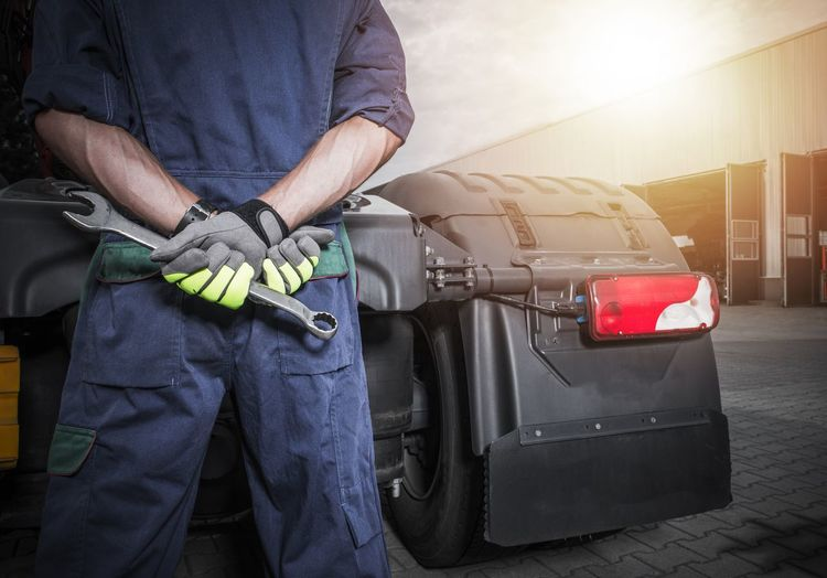 Broken Truck Problem. Semi Trucks Mechanic with Large Wrench Looking For Ideas How to Fix the Problem. Mechanic Service Transportation Adult Broken Day Fuel Pump Men One Person Outdoors People Refueling Semi Truck Servicing Standing Trucking